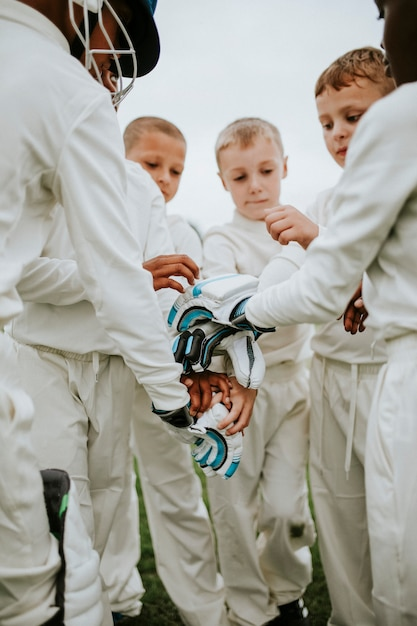 Young cricketer stacking their hands together Premium Photo