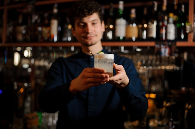 Young curly barman holding a glass with fresh and sour summer cocktail Premium Photo