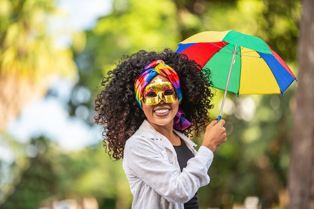 Young curly hair woman celebrating the brazilian carnival party with frevo umbrella on street. Premium Photo