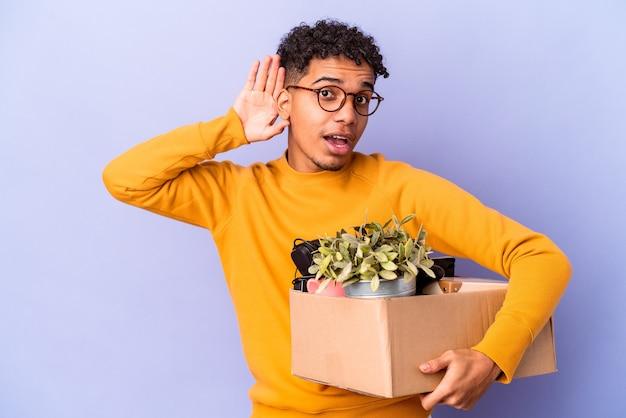 ゴシップを聞いて新しい家に移動する孤立した若い巻き毛の男 Premium写真