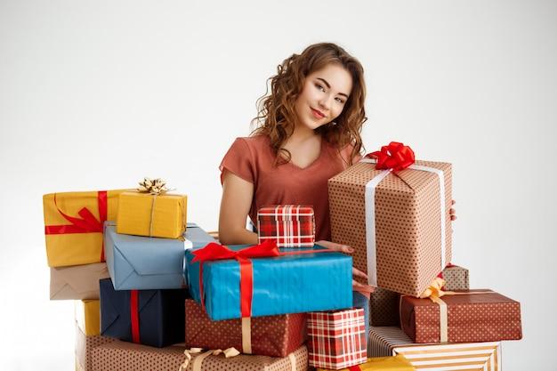 Молодая кудрявая женщина среди подарочных коробок на белом Бесплатные Фотографии