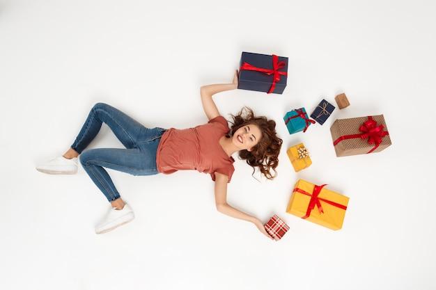 선물 상자 가운데 누워 젊은 곱슬 여자 무료 사진