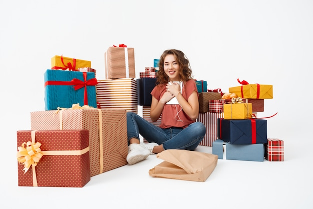 Young curly woman sitting on floor among gift boxes with just opened present tablet Free Photo