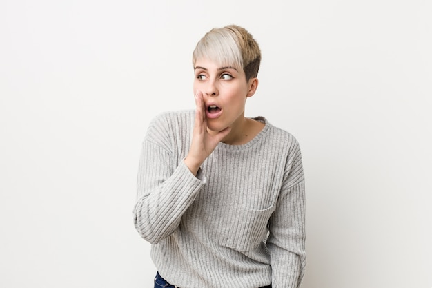 Young curvy caucasian woman isolated on white  is saying a secret hot braking news and looking aside Premium Photo