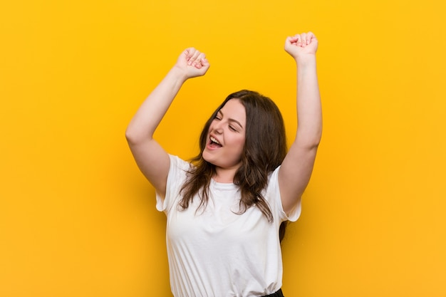 Young curvy plus size woman celebrating a special day, jumps and raising arms with energy. Premium Photo