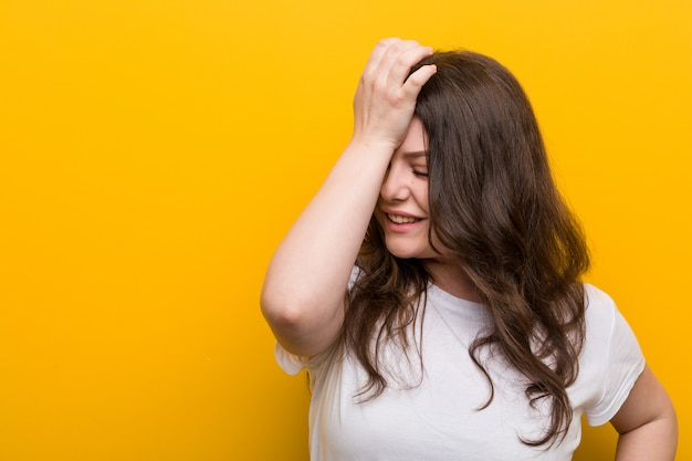 Young curvy plus size woman forgetting something, slapping forehead with palm and closing eyes. Premium Photo