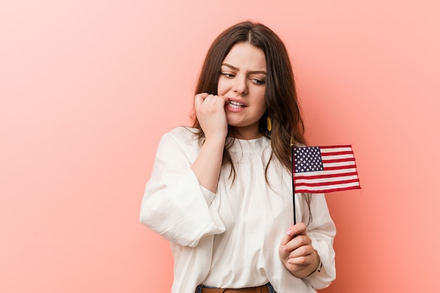 Young curvy plus size woman holding a united states flag biting fingernails, nervous and very anxious. Premium Photo