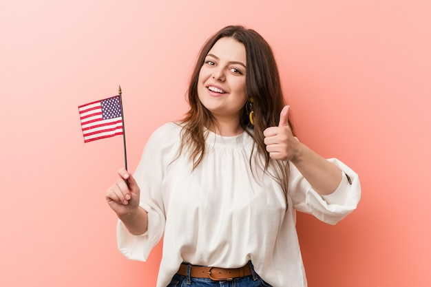 Young curvy plus size woman holding a united states flag smiling and raising thumb up Premium Photo
