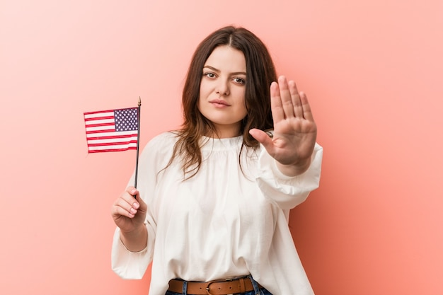Young curvy plus size woman holding a united states flag standing with outstretched hand showing stop sign, preventing you. Premium Photo