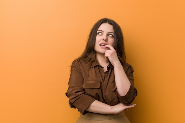 Young curvy russian woman relaxed thinking about something looking at a copy space.