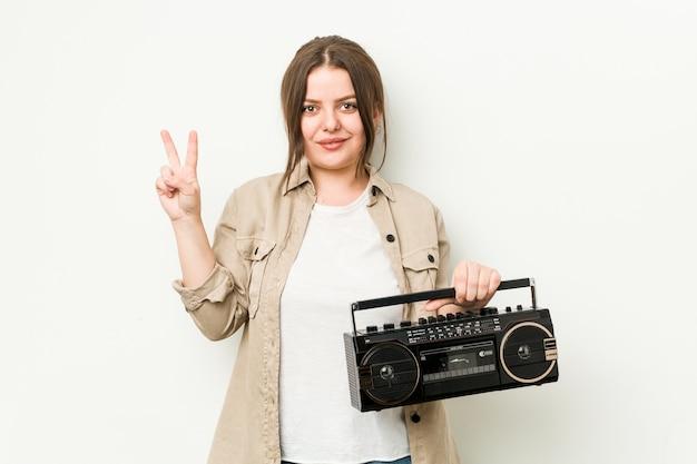 Молодая соблазнительная женщина, держащая ретро-радио, показывая пальцами номер два. Premium Фотографии