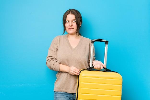 Молодая пышная женщина, держащая чемодан, смущена, чувствует себя сомнительно и неуверенно. Premium Фотографии