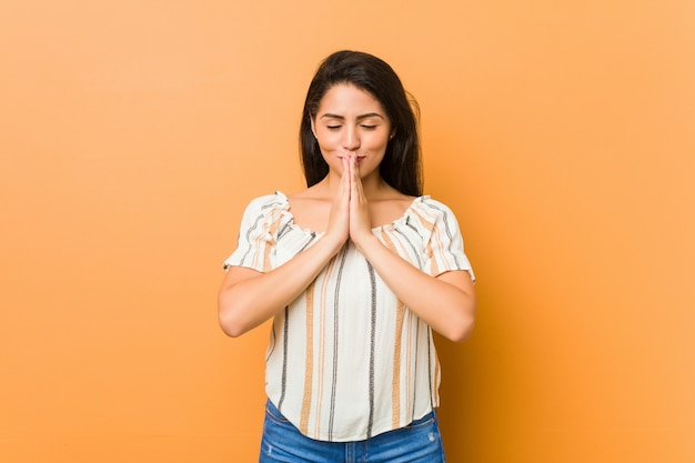 Young curvy woman holding hands in pray near mouth, feels confident. Premium Photo