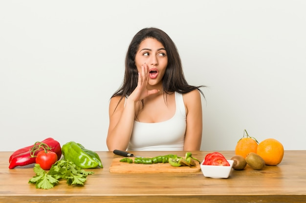Young curvy woman preparing a healthy meal is saying a secret hot braking news and looking aside Premium Photo