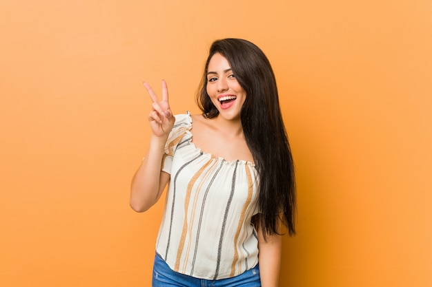 Young curvy woman showing victory sign and smiling broadly. Premium Photo