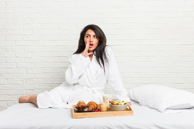 Young curvy woman taking a breakfast on the bed is saying a secret hot braking news and looking aside Premium Photo
