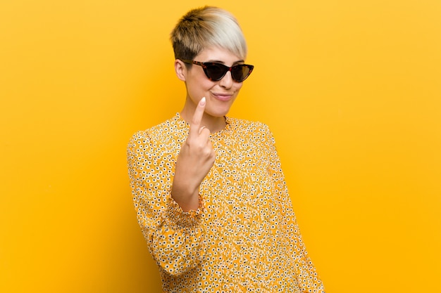 Young curvy woman wearing a floral summer clothes pointing with finger at you as if inviting come closer. Premium Photo