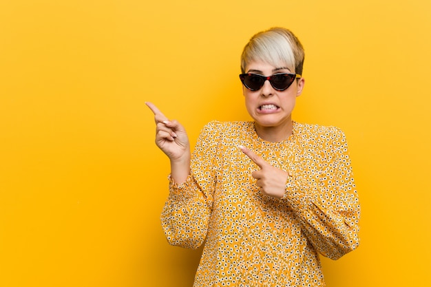 Young curvy woman wearing a floral summer clothes shocked pointing with index fingers to a copy space. Premium Photo