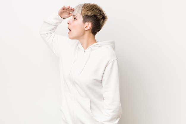 Young curvy woman wearing a white hoodie looking far away keeping hand on forehead. Premium Photo