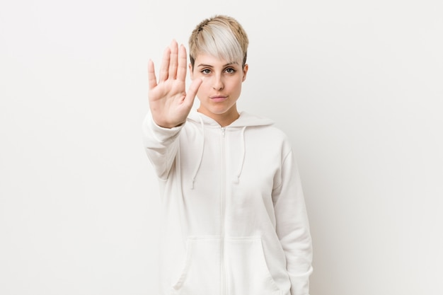 Young curvy woman wearing a white hoodie standing with outstretched hand showing stop sign, preventing you. Premium Photo