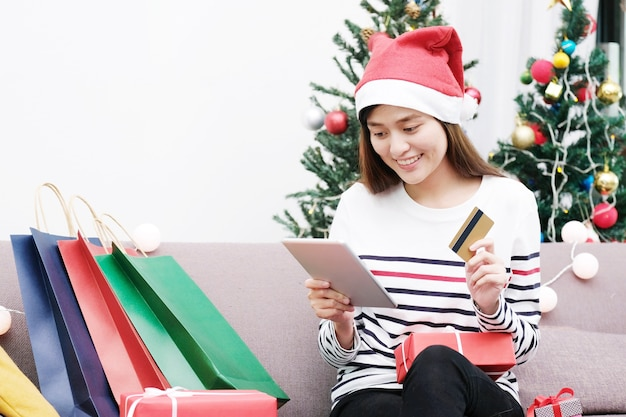 746b38a06ff2d Young cute asian woman wearing santa hat and shopping online. Premium Photo