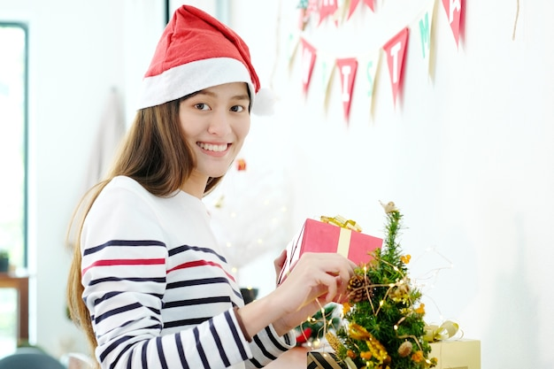 136e09bb20ff7 Young cute asian woman wearing santa hat smiling while decorating christmas  tree. Premium Photo