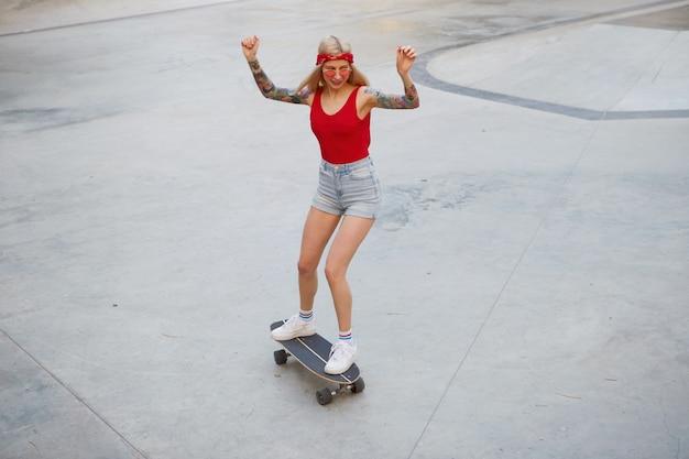 Молодая симпатичная блондинка с татуированными руками в красной футболке и джинсовых шортах с вязанной банданой на голове, в красных очках, с поднятыми руками, наслаждается днем и катается на лонгборде в скейт-парке. Бесплатные Фотографии