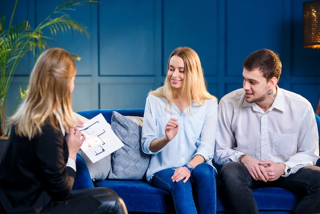 Young cute family on the meeting with realtor, interior designer, decorator. Premium Photo