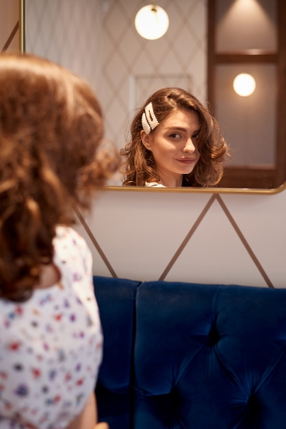 Young Cute Girl Smiling And Looking At Herself In The Mirror