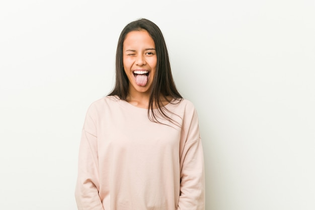 Young cute hispanic teenager woman funny and friendly sticking out tongue. Premium Photo