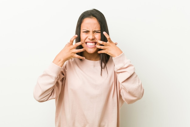 Young cute hispanic teenager woman upset screaming with tense hands. Premium Photo