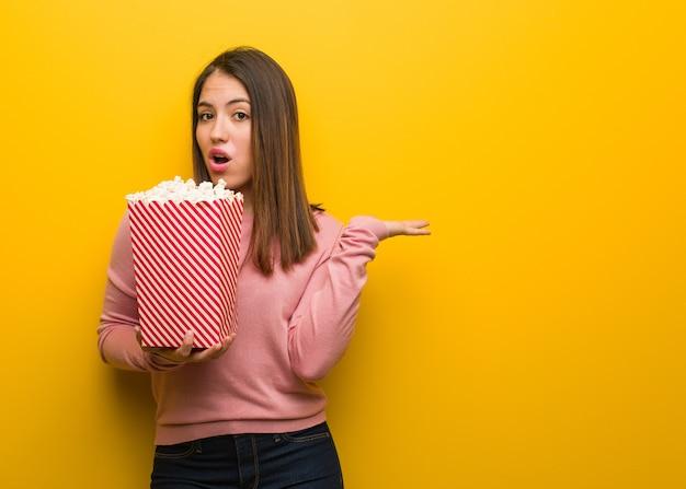 Молодая милая женщина держит ведро попкорна, держа что-то на ладони Premium Фотографии