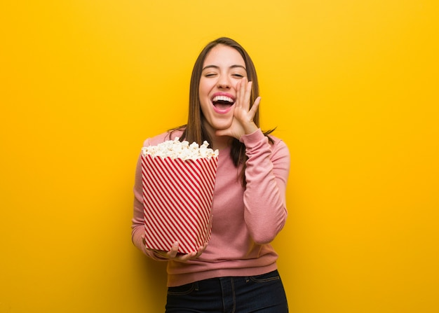 Young cute woman holding a popcorn bucket shouting something happy to the front Premium Photo