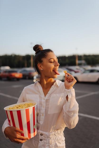 ショッピングモールの駐車場でポップコーンを保持している若いかわいい女性 無料写真