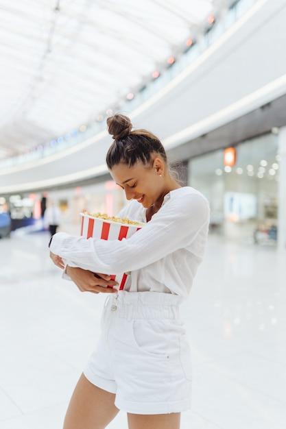 Giovane donna carina con popcorn sullo sfondo del centro commerciale Foto Gratuite