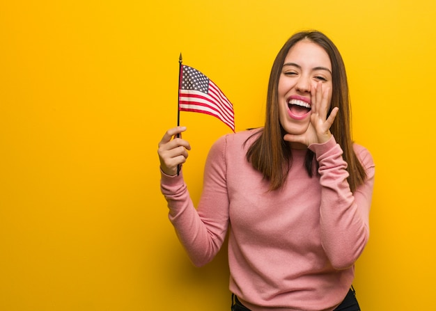 Young cute woman holding an united states flag shouting something happy to the front Premium Photo