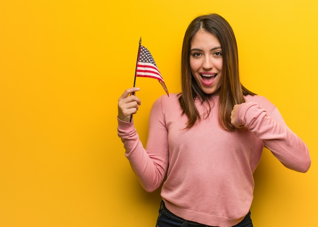 Young cute woman holding an united states flag surprised, feels successful and prosperous Premium Photo