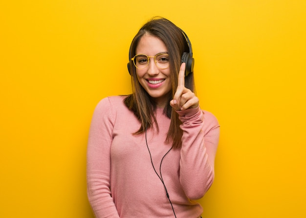 Young cute woman listening to music showing number one Premium Photo