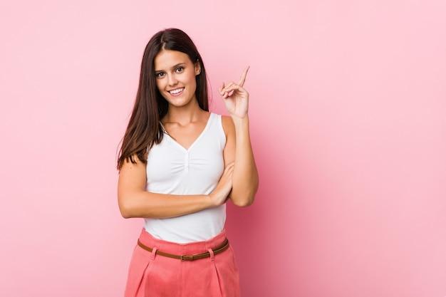 Молодая милая женщина улыбается, весело указывая указательным пальцем. Premium Фотографии