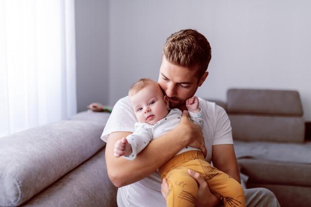 Молодой папа держит своего любящего очаровательного сына, сидя на диване в гостиной Premium Фотографии