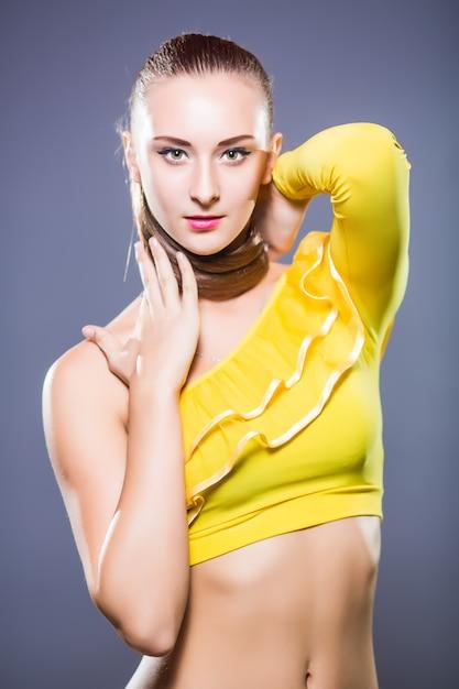 Молодой танцор со спортивным телом позирует в студии на белом фоне Бесплатные Фотографии