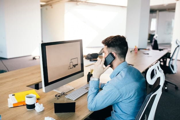 Young dark-haired man is working with a computer and talking on the phone at his desktop in office. he wears blue shirt and looks busy. Free Photo
