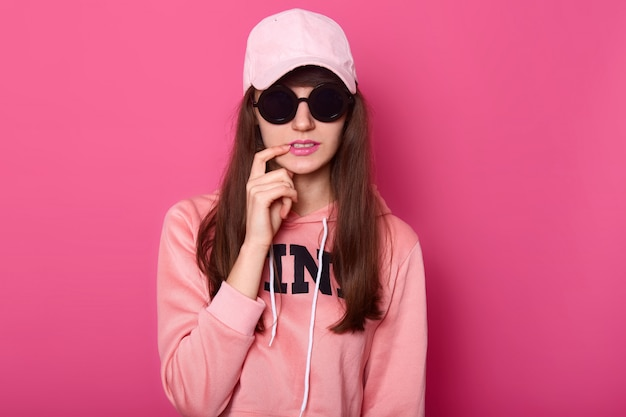Young dark haired teenager girl wearing stylish pink hoodie Free Photo