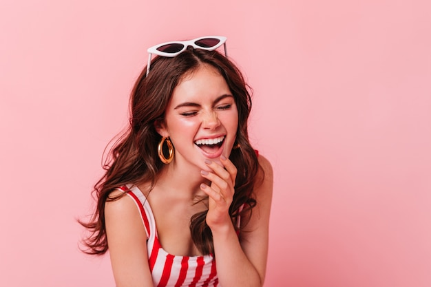Young dark-haired woman in great mood is laughing with closed eyes on pink wall Free Photo