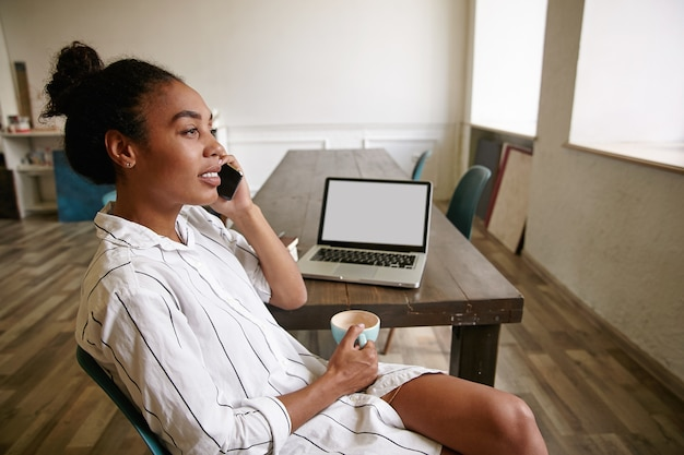 Giovane imprenditrice dalla pelle scura facendo pausa mentre si lavora nella sala riunioni, tenendo la tazza di caffè e facendo chiamate con il suo smartphone, guardando calmo e concentrato Foto Gratuite