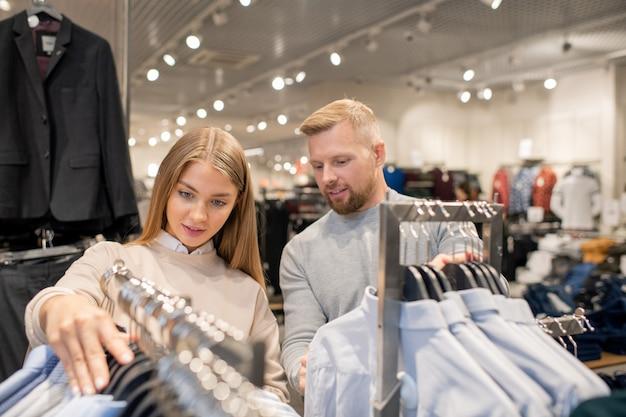レジャーで大規模な貿易センターを訪れながら、ラックに掛かっているシャツのコレクションを見ている若いデート Premium写真
