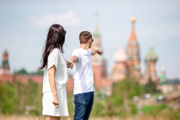 Young dating couple in love walking in city background st basils church Premium Photo