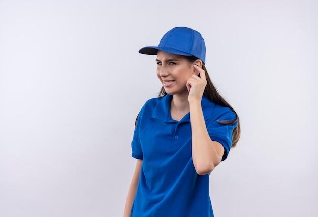 Giovane ragazza delle consegne in uniforme blu e tappo che chiude l'orecchio con il dito con espressione infastidita Foto Gratuite