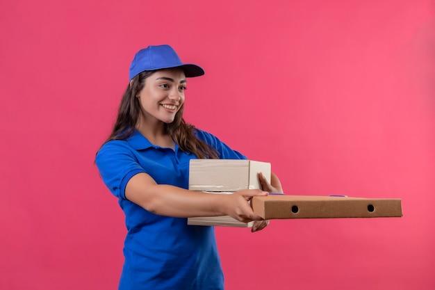 Giovane ragazza di consegna in uniforme blu e cappuccio che dà le scatole di cartone ad un cliente che sorride amichevole che sta sopra fondo rosa Foto Gratuite