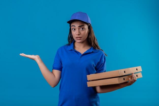 Giovane ragazza delle consegne in uniforme blu e cappuccio che tiene le scatole per pizza in piedi senza tracce e confuse con il braccio alzato senza risposta su sfondo blu Foto Gratuite